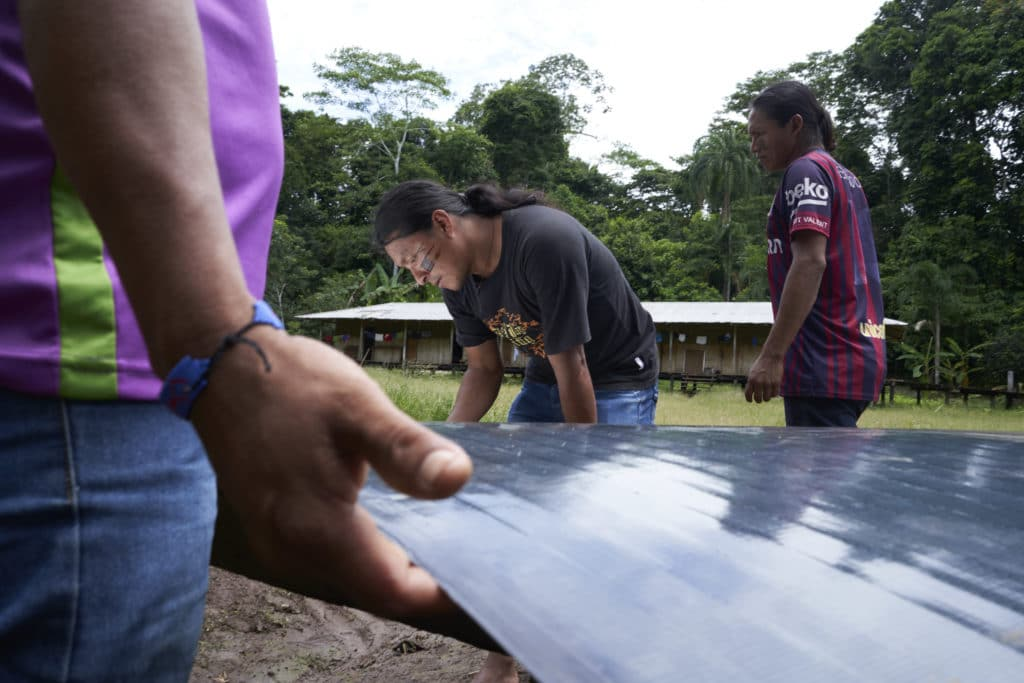 three men working on a solar panel