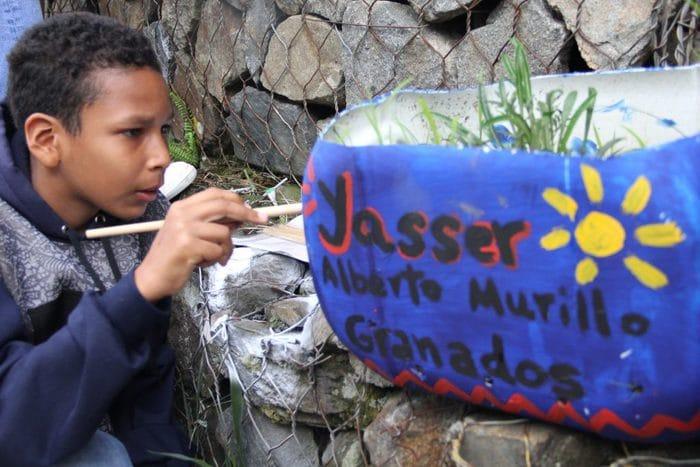 A kid paints a vase in Medellín - Agroarte Colombia